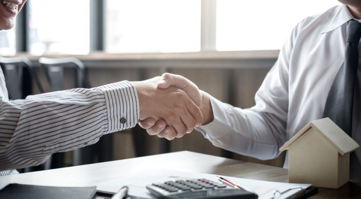 image of a mortgage broker shaking hands with a new homeowner