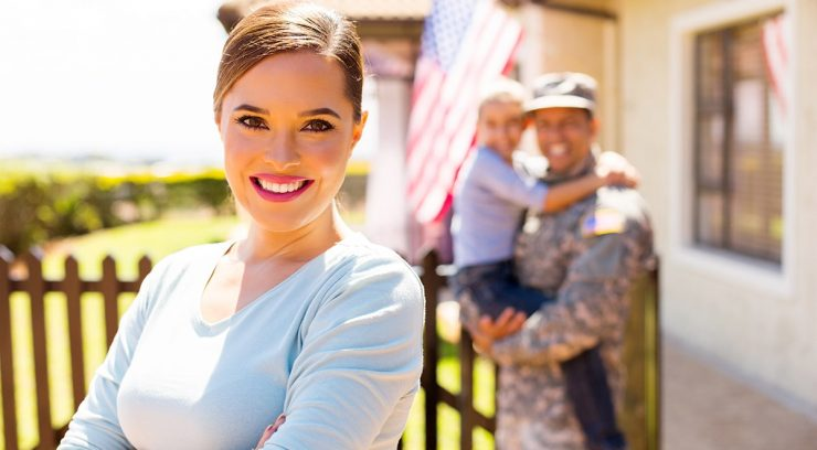 image of a veteran standing in front of her new home with her family